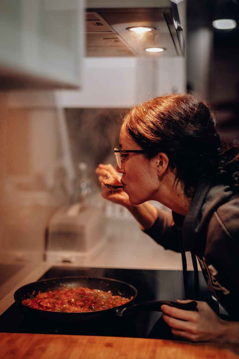 woman eating on cooking pan